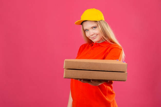 Młoda kobieta dostawy ubrana w czerwoną koszulkę polo i żółtą czapkę wyciągając stos pudełek po pizzy z uśmiechem na twarzy na izolowanych różowym tle