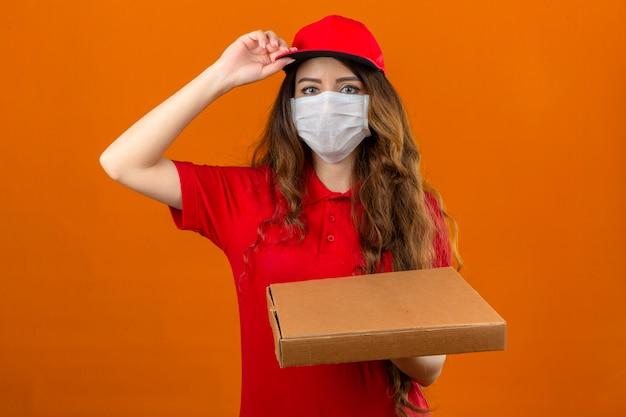 Młoda kobieta dostawy ubrana w czerwoną koszulkę polo w medycznej masce ochronnej zakładając czapkę stojącą ze stosem pudełek po pizzy, patrząc pewnie na pojedyncze pomarańczowe tło