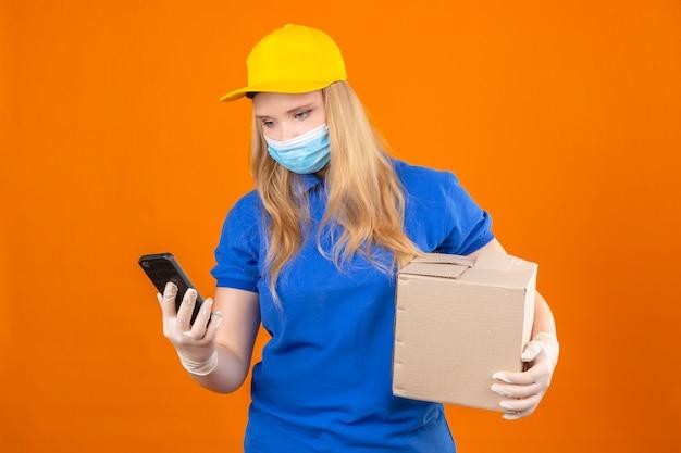 Młoda kobieta dostawy ubrana w niebieską koszulkę polo i żółtą czapkę w medycznej masce ochronnej stojąca z tekturowym pudełkiem patrząc na ekran swojego smartfona na odosobnionym ciemnożółtym tle