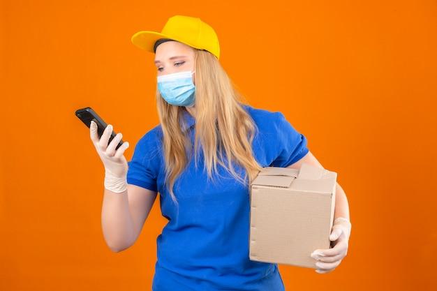 Młoda kobieta dostawy ubrana w niebieską koszulkę polo i żółtą czapkę w medycznej masce ochronnej stojąca z tekturowym pudełkiem patrząc na ekran swojego smartfona z uśmiechem na izolowanym ciemnożółtym backg