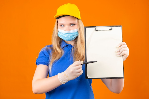 Młoda kobieta dostawy ubrana w niebieską koszulkę polo i żółtą czapkę w medycznej masce ochronnej, stojąca ze schowkiem, wskazująca piórem z prośbą o podpis z poważną twarzą nad odizolowaną ciemnożółtą