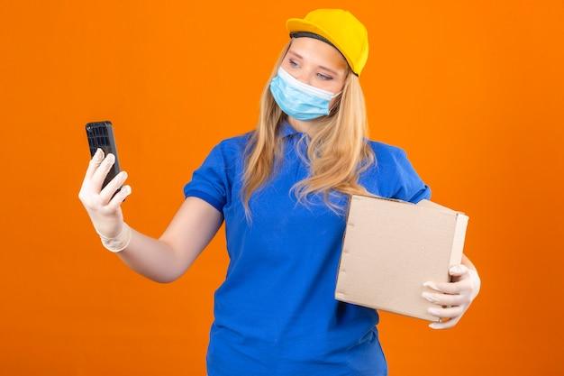 Młoda kobieta dostawy ubrana w niebieską koszulkę polo i żółtą czapkę w medycznej masce ochronnej stojącej z tekturowym pudełkiem, biorąc selfie na smartfonie na izolowanym ciemnożółtym tle
