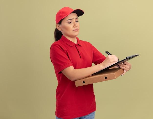 Młoda kobieta dostawy w czerwonym mundurze i czapce trzyma pudełko po pizzy ze schowka i ołówkiem patrząc z poważną twarzą stojącą nad zieloną ścianą