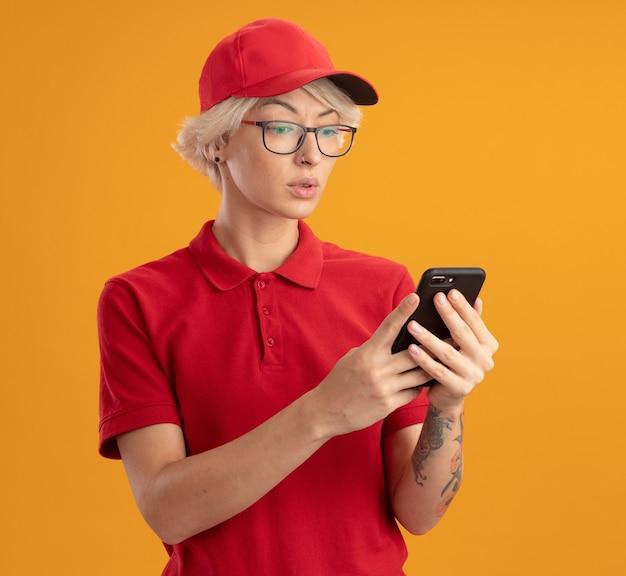 Młoda kobieta dostawy w czerwonym mundurze i czapce w okularach, patrząc na swojego smartfona z poważną twarzą stojącą na pomarańczowej ścianie