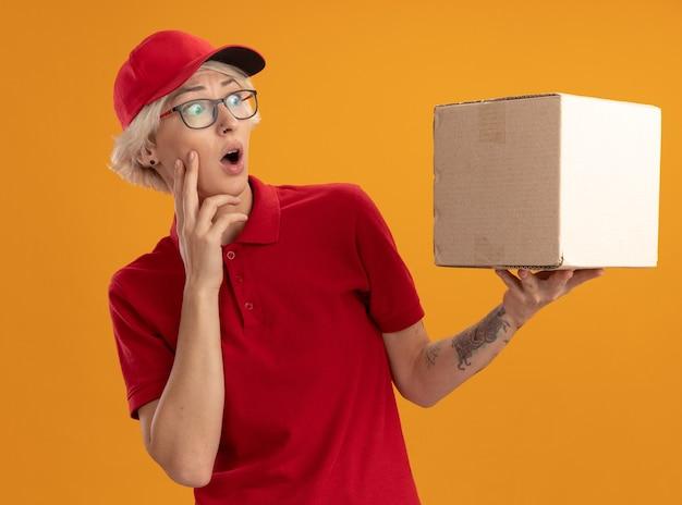 Młoda kobieta dostawy w czerwonym mundurze i czapce w okularach trzyma karton patrząc na niego zdumiony i zaskoczony stojąc nad pomarańczową ścianą