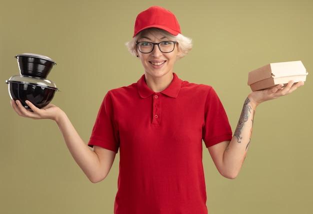 Młoda kobieta dostawy w czerwonym mundurze i czapce w okularach, trzymając opakowania żywności, uśmiechając się radośnie stojąc na zielonej ścianie
