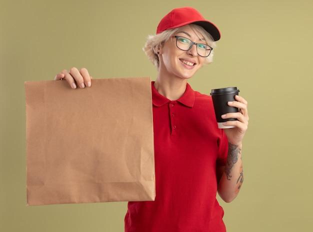 Młoda kobieta dostawy w czerwonym mundurze i czapce w okularach, trzymając pakiet papieru i filiżankę kawy, uśmiechając się czule stojąc nad zieloną ścianą