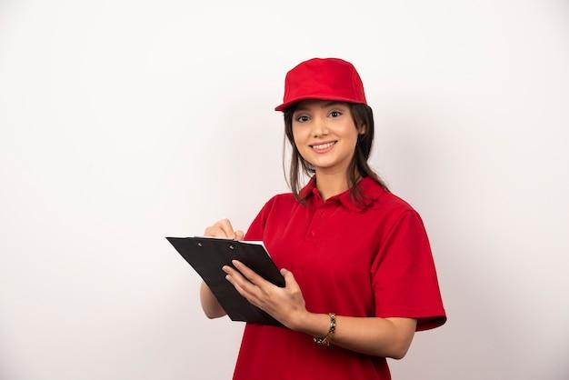Młoda kobieta dostawy w czerwonym mundurze ze schowka na białym tle.
