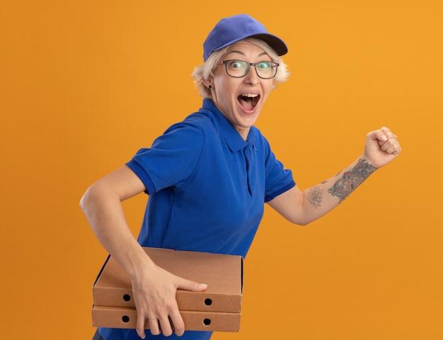 Młoda kobieta dostawy w niebieskim mundurze i czapce jest podekscytowana biegiem do dostarczania pudełek po pizzy dla klienta na pomarańczowej ścianie