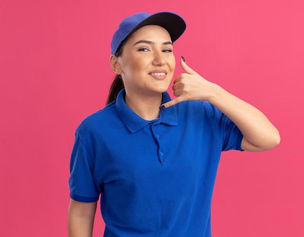 Młoda kobieta dostawy w niebieskim mundurze i czapce patrząc na przód uśmiechnięta wesoło, wykonując wezwanie do mnie gest stojąc nad różową ścianą