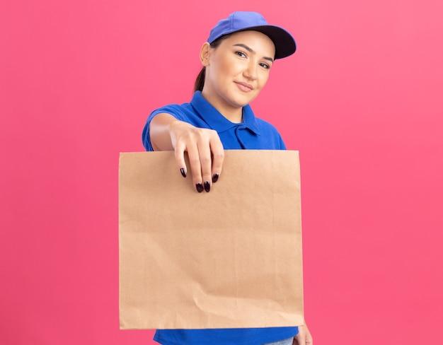Młoda kobieta dostawy w niebieskim mundurze i czapce trzyma papierową paczkę patrząc na przód uśmiechnięta pewnie stojąca nad różową ścianą