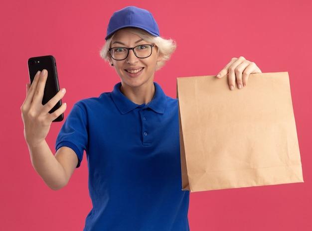 Młoda kobieta dostawy w niebieskim mundurze i czapce, trzymając papierowy pakiet i smartfon z uśmiechem na twarzy stojącej nad różową ścianą