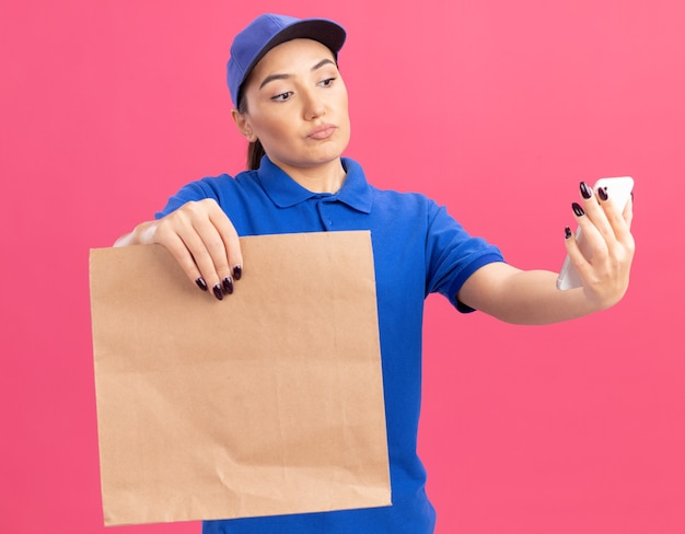 Młoda kobieta dostawy w niebieskim mundurze i czapce, trzymając papierowy pakiet patrząc na swojego smartfona z poważną twarzą stojącą nad różową ścianą