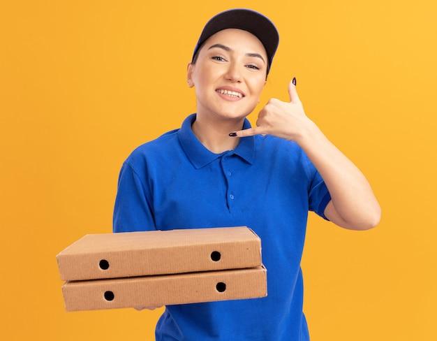 """Młoda kobieta dostawy w niebieskim mundurze i czapce trzymająca pudełka po pizzy patrząc z przodu, uśmiechnięta wesoło, pokazująca gest """"zadzwoń do mnie"""" ręką stojącą nad pomarańczową ścianą"""