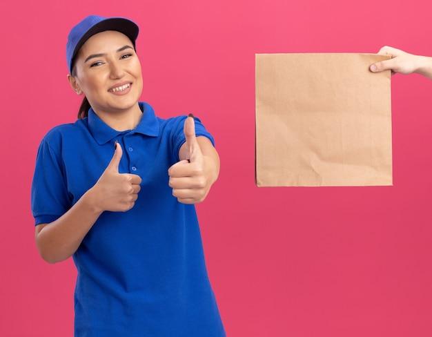Młoda kobieta dostawy w niebieskim mundurze i czapce uśmiechnięty przyjazny pokazując kciuki do góry podczas odbierania pakietu papieru stojącego nad różową ścianą