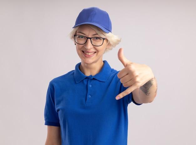 Młoda kobieta dostawy w niebieskim mundurze i czapce w okularach patrząc uśmiechnięty z radosną buźką, dzwoniąc do mnie gest stojąc na białej ścianie