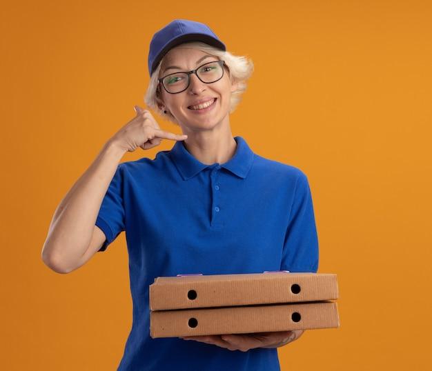 Młoda kobieta dostawy w niebieskim mundurze i czapce w okularach, trzymając pudełka po pizzy, uśmiechając się, robiąc cal me gest uśmiechnięty nad pomarańczową ścianą