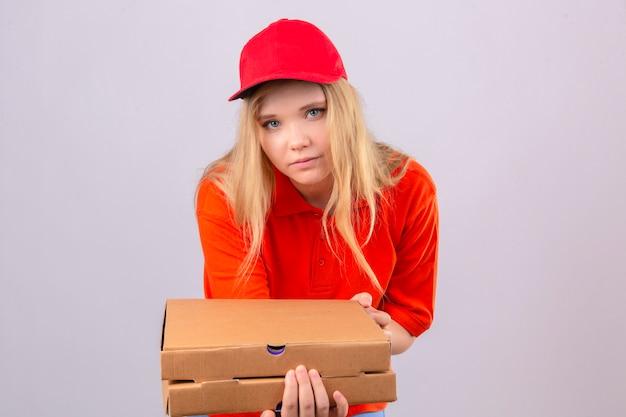 Młoda kobieta dostawy w pomarańczowej koszulce polo i czerwonej czapce patrząc na kamery wyciągając stos pudełek po pizzy na białym tle