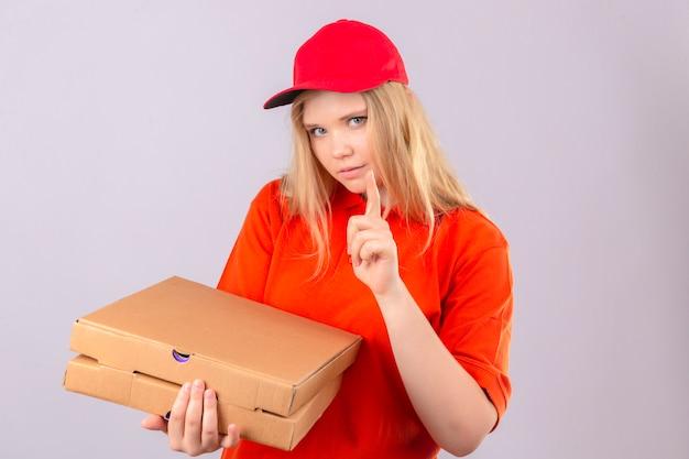 Młoda kobieta dostawy w pomarańczowej koszulce polo i czerwonej czapce stojącej z pudełkami po pizzy skierowanymi w górę palcem wskazującym, patrząc na kamerę z poważną twarzą na izolowanym białym tle