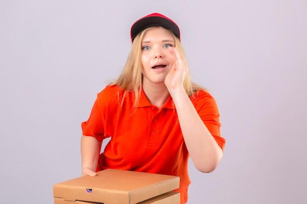 Młoda kobieta dostawy w pomarańczowej koszulce polo i czerwonej czapce stojącej z pudełkami po pizzy, trzymając rękę w pobliżu otwartych ust i mówiąc coś na odosobnionym białym tle