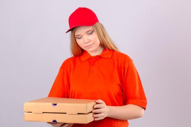 Młoda kobieta dostawy w pomarańczowej koszulce polo i czerwonej czapce trzyma pudełka po pizzy patrząc z uśmiechem na twarzy na na białym tle