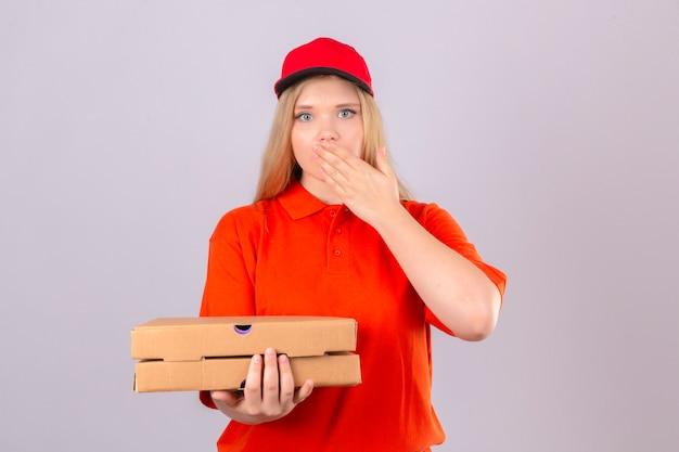 Młoda kobieta dostawy w pomarańczowej koszulce polo i czerwonej czapce, trzymając pudełka po pizzy, patrząc zaskoczony, zakrywając usta ręką na białym tle
