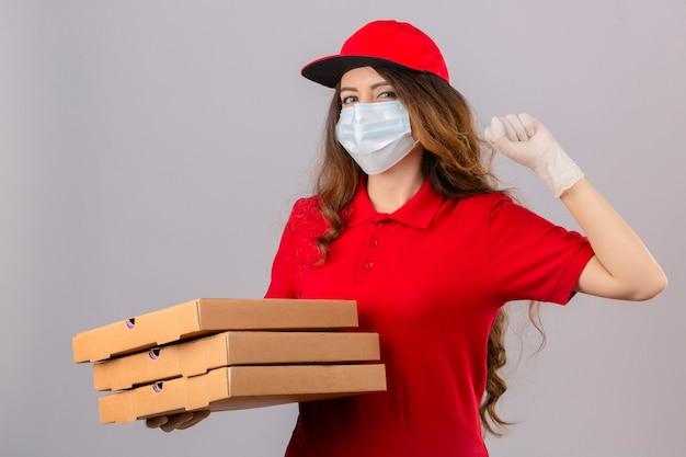 Młoda kobieta dostawy z kręconymi włosami, ubrana w czerwoną koszulkę polo i czapkę w medycznej masce ochronnej i rękawiczkach, stojąca z pudełkami po pizzy, podnosząca pięść po zwycięstwie koncepcja zwycięzcy szczęśliwej twarzy nad izolacją