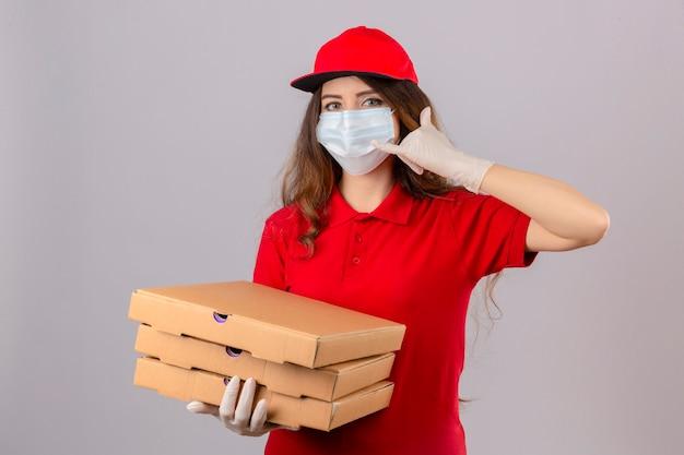 Młoda kobieta dostawy z kręconymi włosami, ubrana w czerwoną koszulkę polo i czapkę w medycznej masce ochronnej i rękawiczkach z pudełkami po pizzy, wykonująca gest zadzwoń do mnie, wyglądająca pewnie na białym tle
