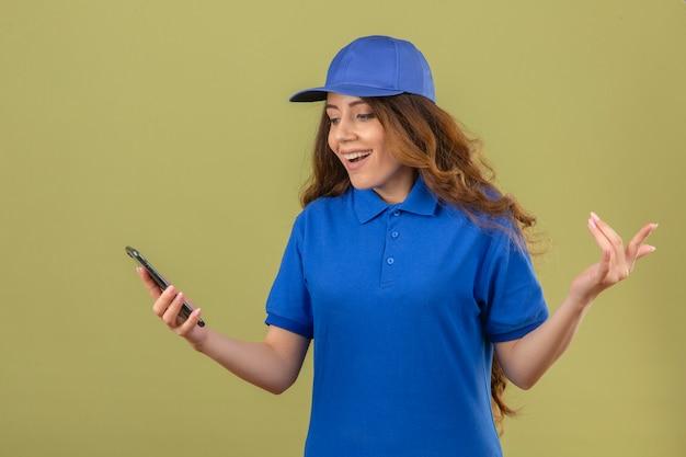 Młoda kobieta dostawy z kręconymi włosami, ubrana w niebieską koszulkę polo i czapkę, patrząc na ekran smartfona zaskoczona, uśmiechnięta z radosną twarzą z ręką uniesioną nad odizolowanym zielonym tłem