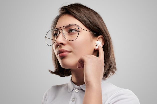Młoda kobieta dostosowująca słuchawki douszne tws