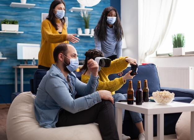 Młoda kobieta doświadcza wirtualnej rzeczywistości, grając w gry wideo z zestawem słuchawkowym vr i joystickiem w salonie. przyjaciele pijący piwo i śmiejący się, utrzymujący dystans społeczny z powodu globalnej pandemii.