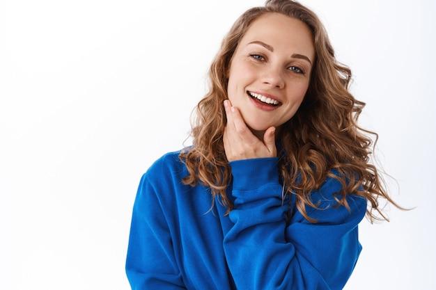 Młoda kobieta dotyka czystej, nawilżonej i odżywionej skóry twarzy i uśmiecha się zadowolona, zadowolona z efektu kosmetyków do pielęgnacji skóry, biała ściana