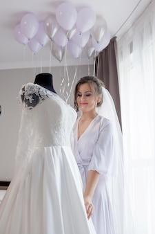 Młoda kobieta dotyka jej ślubną suknię i ono uśmiecha się w jedwabniczym szlafroku podczas gdy stojący blisko okno. dzień ślubu. piękno, moda. najszczęśliwszy dzień ślubu. ciesz się każdą chwilą.