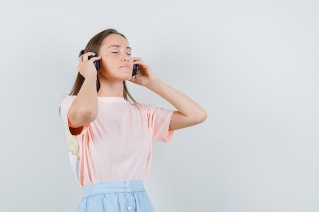 Młoda kobieta dotyka jej słuchawki w t-shirt, spódnicy i wygląda zrelaksowany. przedni widok.