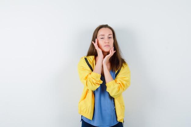 Młoda kobieta dotykając jej skóry twarzy w t-shirt, kurtkę i patrząc intrygujący, widok z przodu.