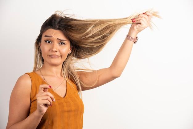 Młoda kobieta dotykając jej włosy i pozowanie na białym tle.