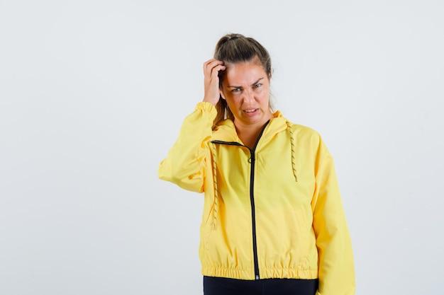 Młoda kobieta drapie się po głowie w żółtym płaszczu przeciwdeszczowym i wygląda na zmartwioną