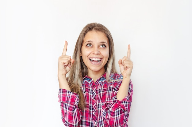 Młoda kobieta dwoma palcami wskazuje na kopię pustego miejsca na tekst lub projekt