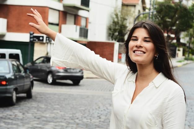 Młoda kobieta dzwoni taxi w ulicie.