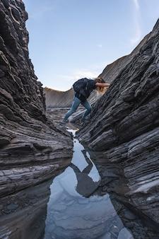Młoda kobieta eksplorująca geopark wybrzeża sakoneta wśród kamieni pewnego ranka