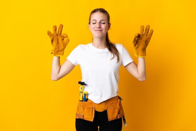 Młoda kobieta elektryk na białym tle na żółtej ścianie w pozie zen