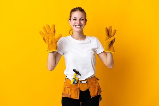 Młoda kobieta elektryk na białym tle na żółty licząc osiem palcami