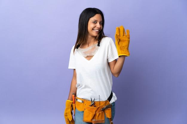 Młoda kobieta elektryk na fioletowym tle salutowania ręką z happy wypowiedzi