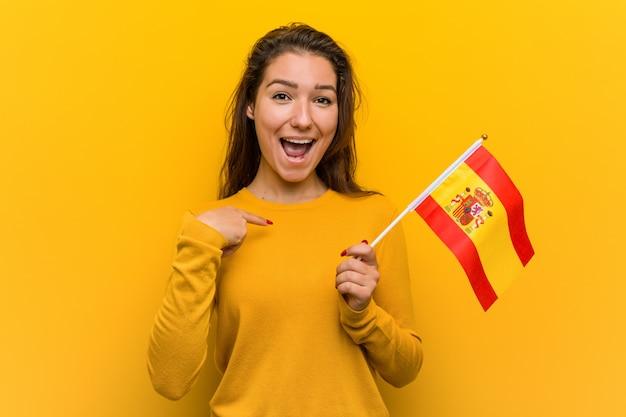 Młoda kobieta europejska trzyma flagę hiszpański zaskoczony, wskazując na siebie, uśmiechając się szeroko.