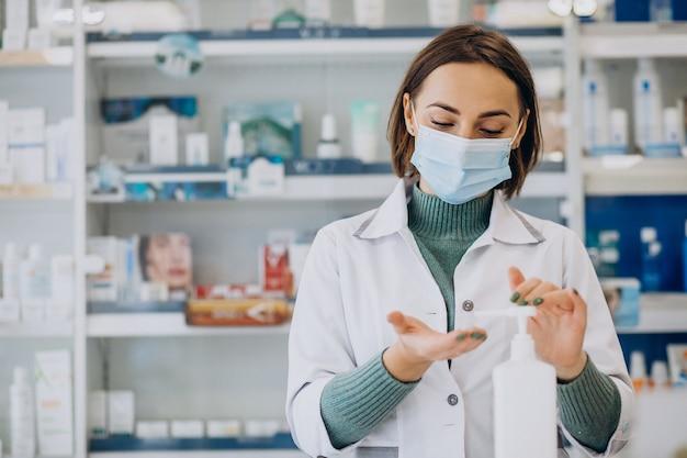 Młoda kobieta farmaceuta dezynfekuje ręce środkiem sanitazer