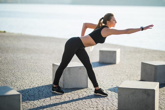 Młoda kobieta fitness biegaczka rozciągająca nogi przed biegiem