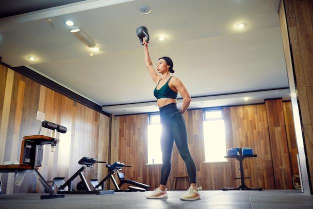 Młoda kobieta fitness dla dorosłych robi huśtawka z kettlebell jako część treningu fitness