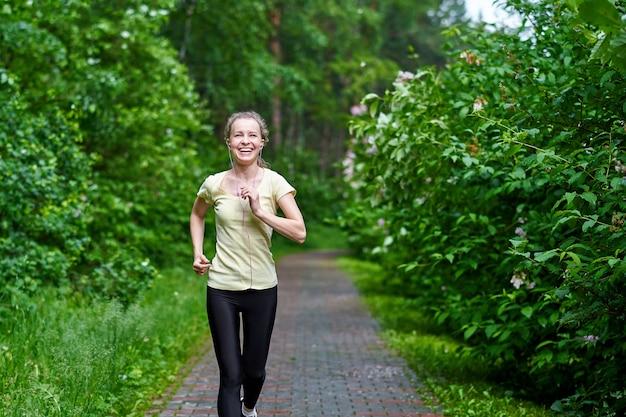 Młoda kobieta fitness działa na leśnym szlaku.