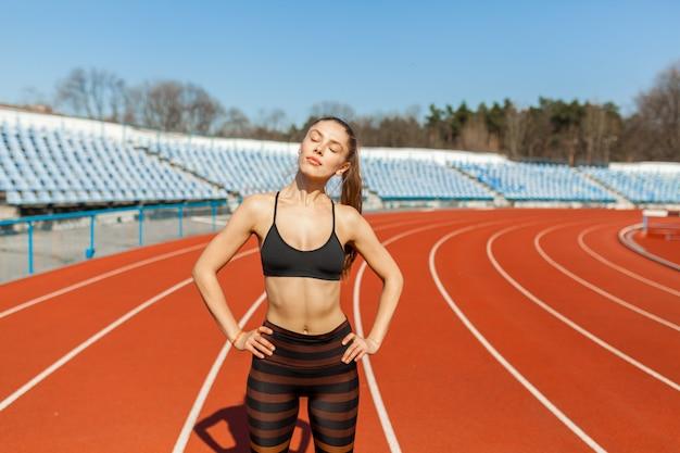 Młoda kobieta fitness lekkoatletka rozgrzać przed uruchomieniem na torze. poranne ćwiczenia w lecie