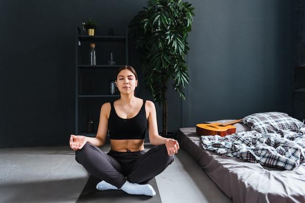 Młoda kobieta fitness medytować, robi joga w domu w domu, blisko łóżka